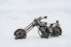 Metal model of a road motorcycle stands on a snowy road, white background
