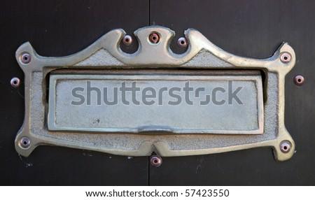 Metal nameplate on wooden door, in Oaxaca