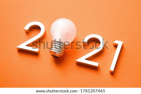 metal numbers 2021 with a burning light bulb. New ideas in the new year.