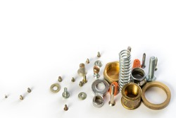 Metal objects on a white background. Details for construction and household repairs. A group of objects lying on the table. Spare parts and parts lying in a pile. Bolts. nuts, screws, spring.