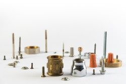Metal objects on a white background. Details for construction and household repairs. A group of objects lying on the table. Spare parts and parts lying in a pile. Bolts. nuts and screws.