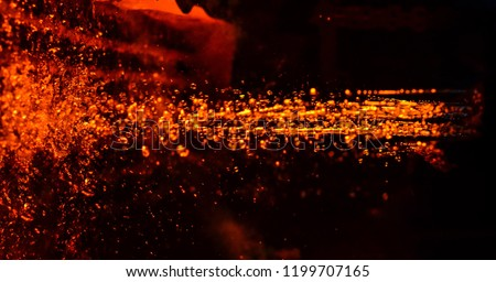 Metal on casting. Metallurgy. Red hot magma texture, red glowing liquid of melt steel iron. Use for abstract background and texture.  High temperature in the melting furnace.