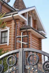 Metal Orthodox cross on the gate against the background of a wooden temple in the city of Voronezh, Russia.
