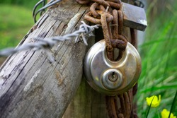 Metal padlock on the gate of private land. The land is owned by a local farmer. The land is next to a public right of a way, a walking path. The gate is wooden and is wrapped in barbed wire. Grass.
