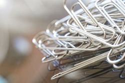 Metal paper clips lie on a reflective glass surface. Office work concept. Macro. Selective focusing. Free space for an inscription. Close-up