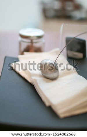 Metal paperweight on stack of white square paper napkin. modern paper napkin holder Close up napkin holder with paperweight to keep brown napkins on black plate and wooden table in coffee shop