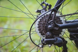 Metal parts of the bike-chain, rear cassette, switch, brakes, gear levers on the background of blurred grass. A sprocket on a Bicycle wheel, a close-up of a Bicycle gearbox and a black electric motor.