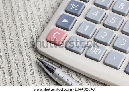 Metal pen and calculator placed on stock data newspaper