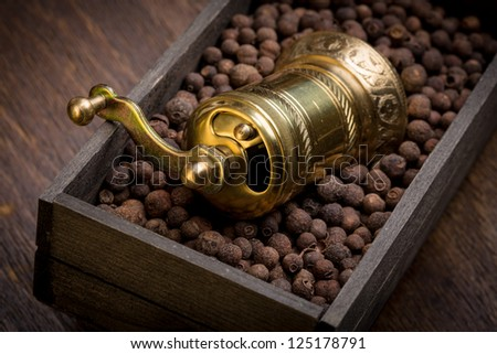 Metal pepper mill in eastern style lying in a wooden box filled with sweet-scented pepper