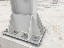 Metal pillar fastened to basement with anchor bolts and nuts. Supporting structures, metal frame of prefabricared building