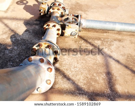 Metal pipes and valves with pipe joints for water supply systems On the cement floor background.