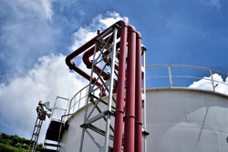 Metal pipes by petroleum storage tank in bright blue sky