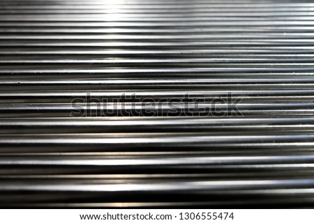 Metal pipes, metal rods steel and iron. Close up shot of a ball bearing. Industrial roller bearing on a light background. Shallow depth of field, selective focus #1306555474