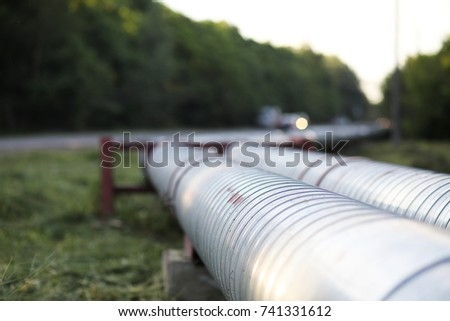 Metal pipes on the street. pipes from the pipeline. gas pipeline for gas pumping. heat-pipe. large silver colored pipe for hot water.