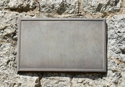 Metal plaque mounted on an old stone wall.