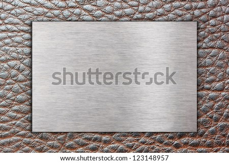 Metal plate on brown leather surface