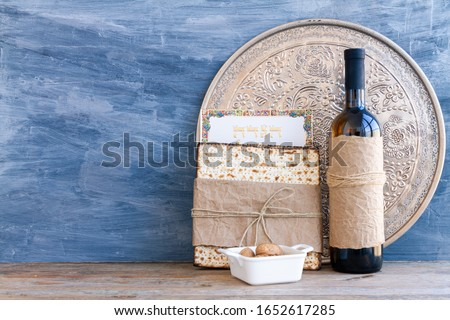Metal plate with matzah or matza and Passover Haggadah on a vintage wood background presented as a Passover seder feast or meal with copy space. Translation: Passover Haggadah
