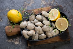 Metal plate with raw fresh vongole clams and lemons on a rustic wooden chopping board, studio shot