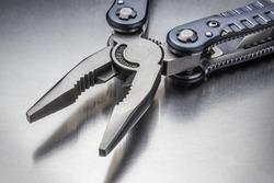 Metal pliers on a metallic background. Hand tool. Tourist equipment.