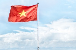 Metal pole with waving banner. Red flag with yellow star, blue sky with clouds in background. Rippled texture. National flag of Vietnam. Popular country for tourism. Famous tourist destination.
