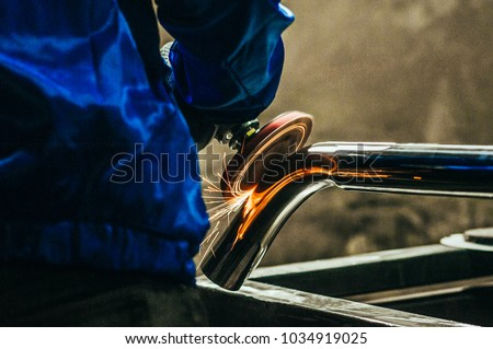 Metal polishing with a hand sander with a polishing disk. Toned image. Hand grinder workflow creation stainless pipe. working process with the sparks