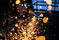 Metal processing in the workshop. Grinding metal. The worker makes the structure of a metal profile. Creating a shelving for the city dweller. Sparks from metal friction.