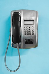 Metal Public Telephone on blue wall. Old payphone concept