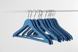 Metal rack with clothes hangers on white background
