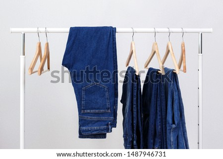 Metal rack with wooden clothes hangers and blue jeans