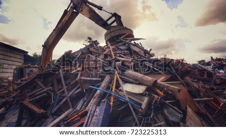 Metal recycle factory, Backhoe use electromagnets crane keeping metal. Vintage filter effect. Environment and save the world concept.