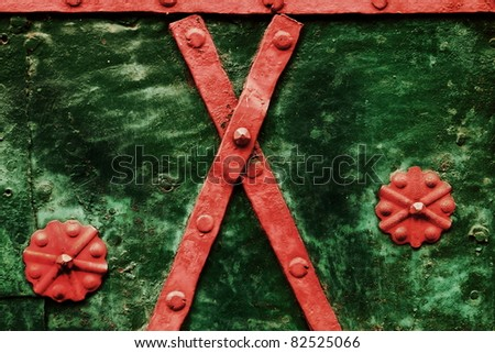 metal red ornaments on the green steel door