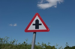 Metal Road Sign for a Crossroads Junction on a Quiet Country Lane with a Bright Blue Sky Background in Rural Devon Countryside, England, UK
