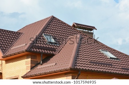 Metal roof with modern house attic construction with roof guttering and attic skylight. window.  Attic skylights. Roofing construction problem area.