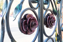 Metal roses decorating forged collars, gate craft element close-up