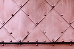 Metal rough background. Dirty pink textured metallic surface of aged carved metal plates with small rivets on them.