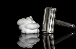 Metal safety razor and white shaving lather foam on top of a reflective glass surface, isolated on black
