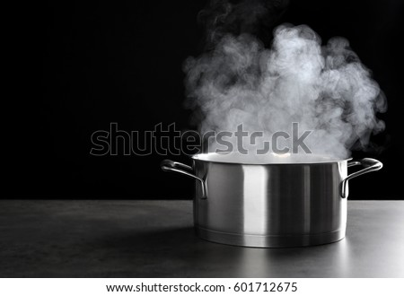 Metal saucepan with hot liquid on table against dark background Сток-фото ©