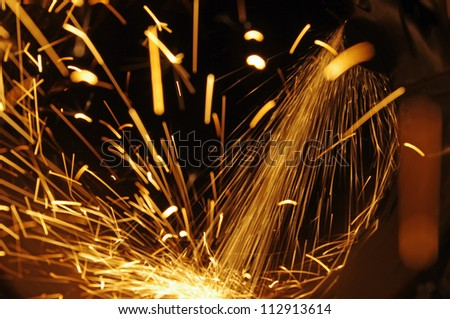 Metal sawing. Hot sparks at grinding steel material. - stock photo