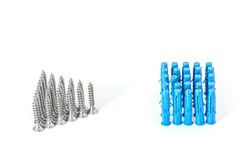 Metal screws are arranged in a triangle and plastic dowels built in a square are opposite each other. Close-up on a white background. Isolated.