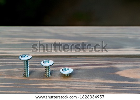 Metal screws with a cap are screwed into a decorative wooden shield