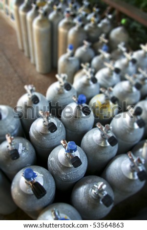 metal scuba diving tanks in dive shop packed close together, shot with narrow depth of field on a full tanks valve