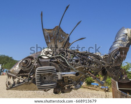 Metal sculpture of fish made of details of old cars (part of sculpture of robot/knight in boat). Camp of bikers. Russia