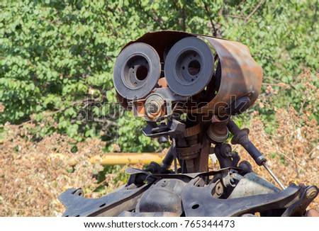 Metal sculpture of trash compactor robot made of rusty details of old cars. Closeup head of robot. Selective focus