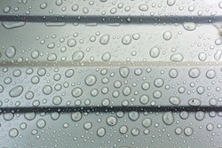 metal sheeting in the rain, large transparent water drops on the metal surface