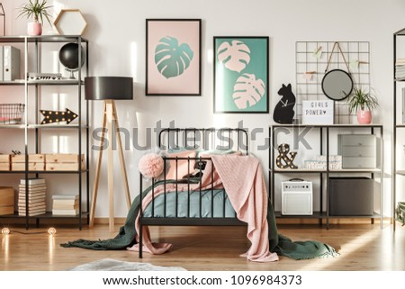 Metal shelves with decorations, botanical posters and comfy bed in a girl bedroom interior #1096984373