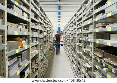 Metal Shelves With Spare Parts And Technician In Plant Interior - stock photo