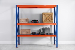 Metal shelving unit with wooden crates and different instruments near light wall indoors