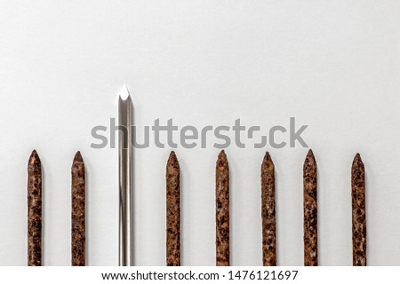 Metal shiny sharp nail stands out in a row of old rusty nails on a light background. Abstract concept of leadership, uniqueness and difference.