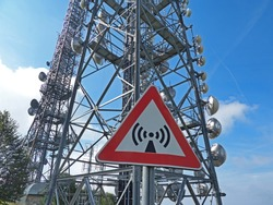 Metal sign with danger of electromagnetic waves. Group of towers for telecommunications, television broadcast, cellphone, radio and satellite on Linzone mountain peak. Telecommunication center