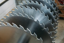 Metal silver circular saw blades for wood work as industrial tool background, close up